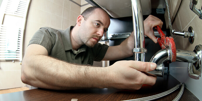 Man Tightening Pipes With Wrench