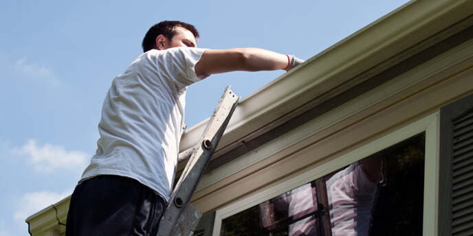 Man on Ladder Cleaning Gutters